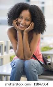 Female university student sitting outside