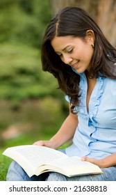 female university student smiling with a book outdoors