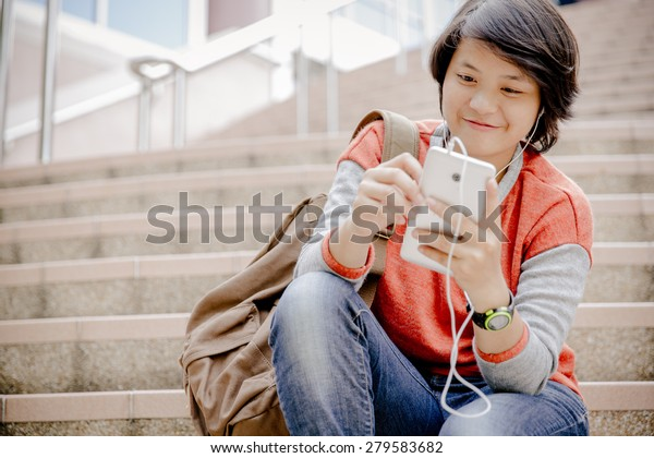 female university student using tablet computer on stairs