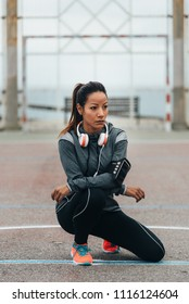 Female urban athlete resting during outdoor workout. Fitness lifestyle and exercising concept. Sporty woman taking a training break.