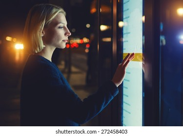 Female using automated teller machine with big digital screen while standing in night city out-of-focus lights,woman verifies account balance on banking application via modern device, filtered image