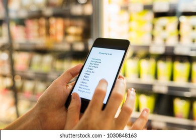 Female using cell phone while shopping in supermarket. Shopping list. Close-up hands. Display fresh food