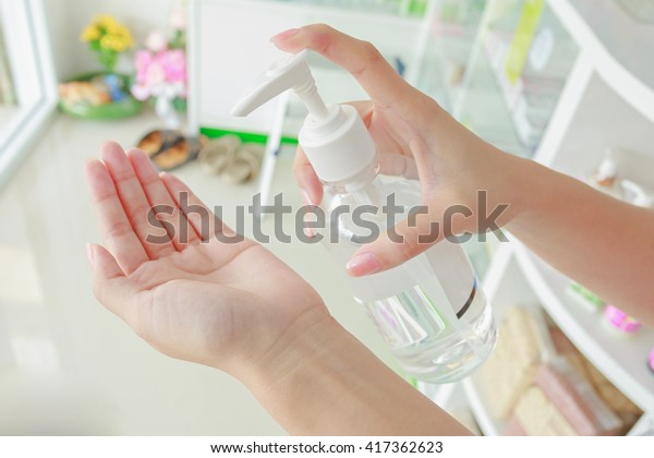 Female using hand press bottle and pouring alcohol-based sanitizer on other hands, Apply all path body, image for aroma spa alternative therapy medicine and meditation aroma concept.