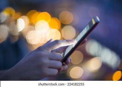 Female using her mobile phone, city skyline night light  background
