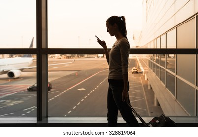 Female using her phone while walking in the airport.