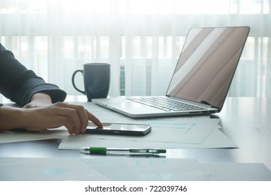 female using mobile smartphone connection while working with laptop in offices, technology and business concepts