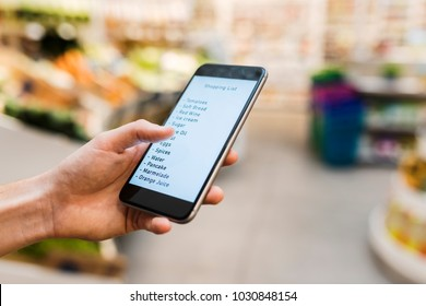 Female using smart phone while shopping in supermarket. Shopping list. Close-up hand