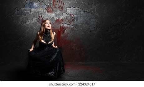 female vampire in front of a bloody wall