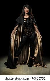Female vampire standing over dark background with spotlight