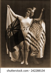 Female vaudeville performer in white body suit, wearing a cape of U.S. and British flags. The 'special relationship' between the two nations solidified in the post civil war era. 1899.
