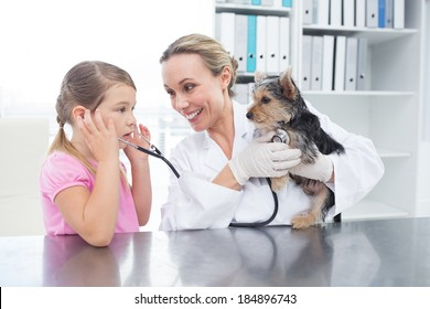 Female vet with girl examining puppy in clinic