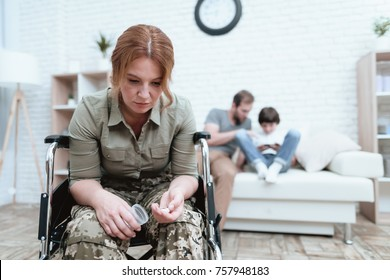 A female veteran in a wheelchair is depressed. She is trying to commit suicide. A woman in uniform is suffering.