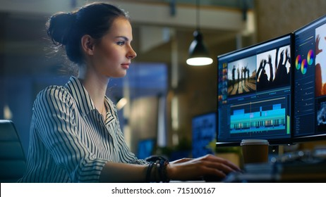 Female Video Editor Works with Footage and Sound on Her Personal Computer. She Works Late. Her Office is Modern and Creative Loft Studio.
