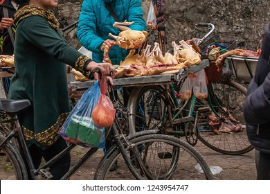 Female vietnamese butcher cutting raw of chicken on a steel tray on bicycle, local street butcher's shop at Lao Kai, North Vietnam. Shallow dept of field. Food culture.