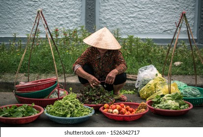 Female Vietnamese street vendor with conical hat selling fruits and vegetables at Hue street market, Hue, Vietnam
