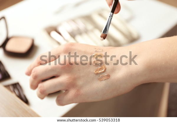Female visagiste applying cosmetics onto hand