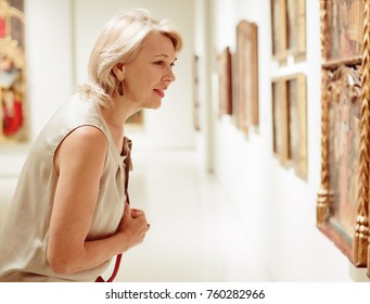 Female visitor looking at artwork painting in the museum indoors