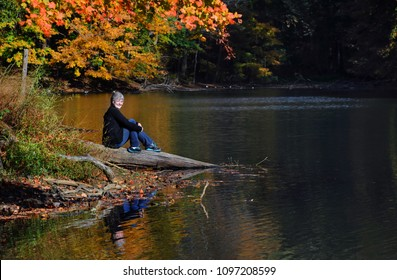 Female visitor smiles, she is sitting quietly on a log besides PoplarTree Lake in Meeman-Shelby State Park near Memphis, Tennessee.