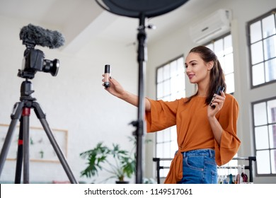 Female vlogger influencer showing product while recording video, promoting advertising using social media platforms