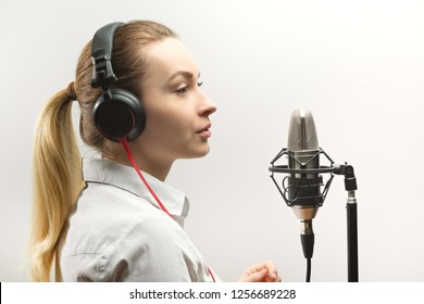Female vocal recording. Young girl with microphone and headphones in recording studio. Recording of vocal, blogger, reading text, voice acting.