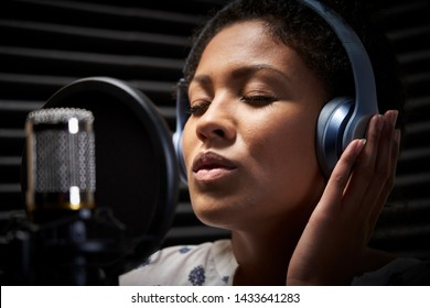 Female Vocalist Wearing Headphones Singing Into Microphone In Recording Studio
