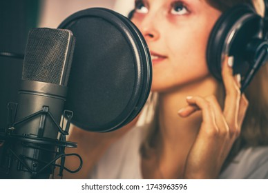 Female Voiceover Speaker in Her 20s Inside Recording Studio in Front of Professional Microphone.