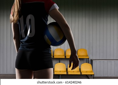 Female volleyball player standing with the ball
