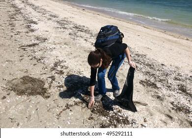 Female volunteer collecting garbage on beach.