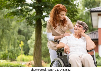 A female volunteer helping an elderly woman in a wheelchair in the garden of an retirement home.