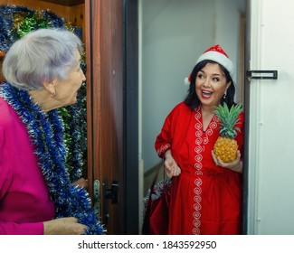 A female volunteer or a kind-hearted neighbor comes to a lonely old woman to wish her a happy Christmas Eve.