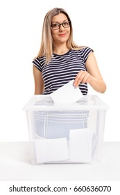 Female voter casting a vote into a ballot box and looking at the camera isolated on white background
