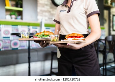 Female waitress is carrying two plates with sandwiches.