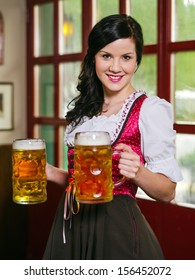 female waitress wearing traditional dirndl and holding huge beers in a pub.