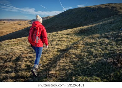 Female Walker hiking across the Black Mountain Range in Wales, UK. Sunset landscape with copy space.