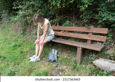 A female walker sits on a wooden bench  with hands on her knees looking tired out. A ruck sack lies on the grass at her feet.She wears shorts and t shirt.Image