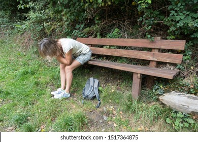 A female walker sits on a wooden bench with her head in her hands and elbows resting on her knees looking tired out. A ruck sack lies on the grass at her feet.She wears shorts and a t shirt.Image