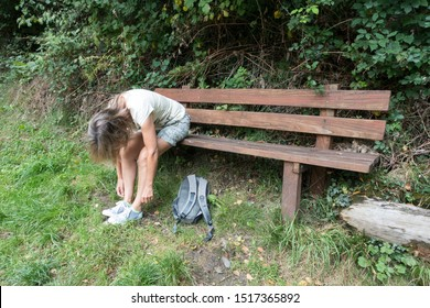 A female walker sits on a wooden bench bent over with arms hanging looking warn out. She wears shorts and a t shirt. A ruck sack lies on the grass at her feet.Image