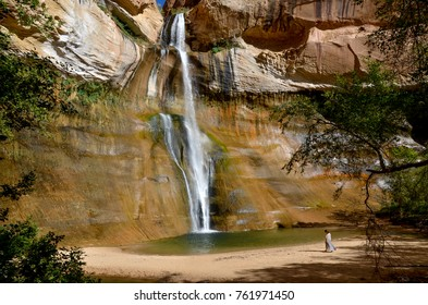 female walking near plunge pool at the bottom of Lower Calf Creek falls  Grand Staircase - Escalante National Monument, Utah