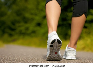 Female walking outdoors in running shoes from behind