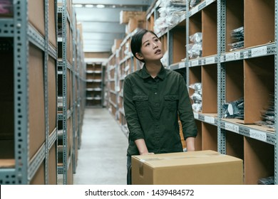 female warehouse worker looking for cardboard and parcels of shelf. young girl staff in stockroom carries collected boxes on cart. lady employee walking in storehouse searching right place for goods.
