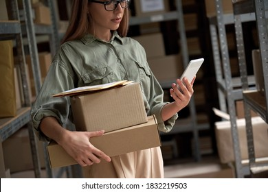 Female warehouse worker manager, small stock business owner holding phone and retail package parcel boxes checking commercial shipping delivery order on smartphone using mobile app technology.
