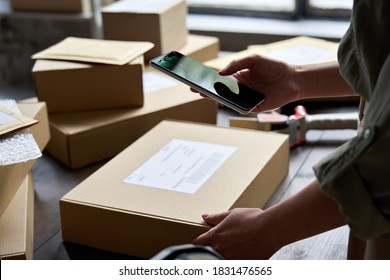 Female warehouse worker seller, small stock business owner holding phone scanning retail package parcel bar code on commercial shipping box delivery order on smartphone using mobile app.