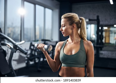 Female watching calmly at her hand holding a steel dumbbell while building the arm muscles