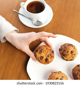 Female weakness. Morning coffee and cake for dessert. Woman holds muffins with raisins. Sweet pastries, dessert. Food concept. Square format or 1x1 for posting on social media.