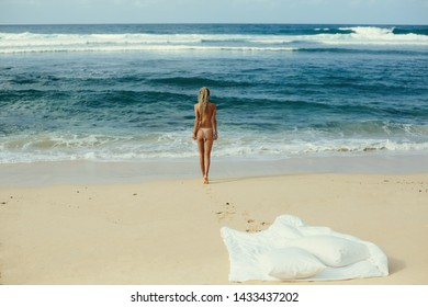 Female wearing dreadlocks walking to water on ocean shore, white blanket on the beach, no clothes, sunny day in paradise