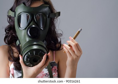 Female wearing a gas mask for protection against the cigarette smoke