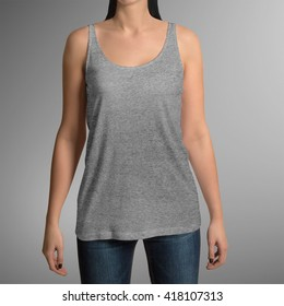 Female wearing grey tank top shirt, isolated on gray background, with clipping path to change background