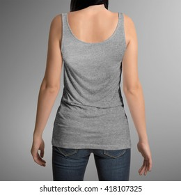 Female wearing grey tank top shirt, back view, isolated on gray background, with clipping path to change background