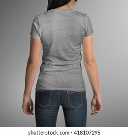 Female wearing grey t-shirt, back view, isolated on gray background, with clipping path to change background
