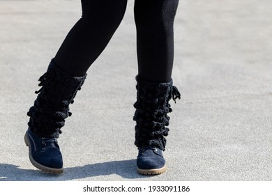 Female is wearing hiking boot and leggings on the street at a cool and dray day.